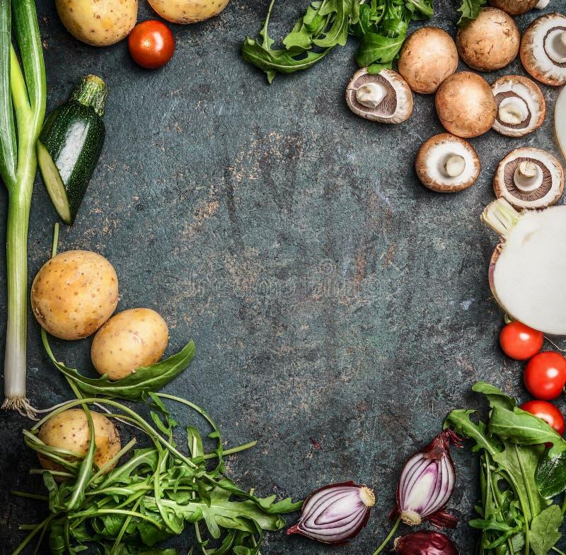 烹调的新鲜的有机季节性庭院菜在土气木背景,顶视图,框架,文本的地方 素食主义者食物 免版税库存图片