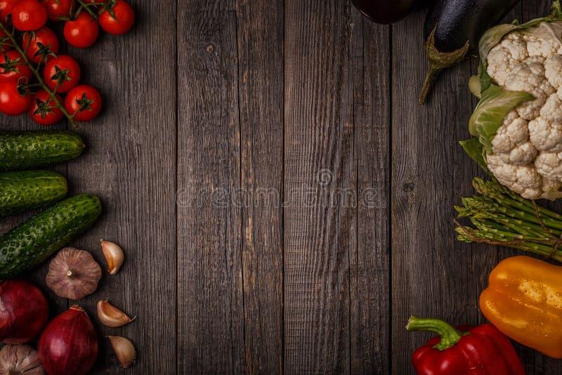 烹调的新鲜蔬菜在黑暗的木背景 免版税图库摄影