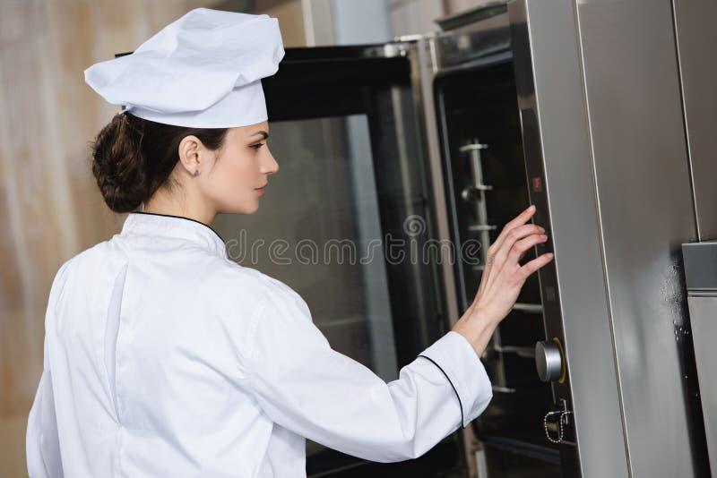 烹调的有吸引力的厨师设置烤箱 库存照片