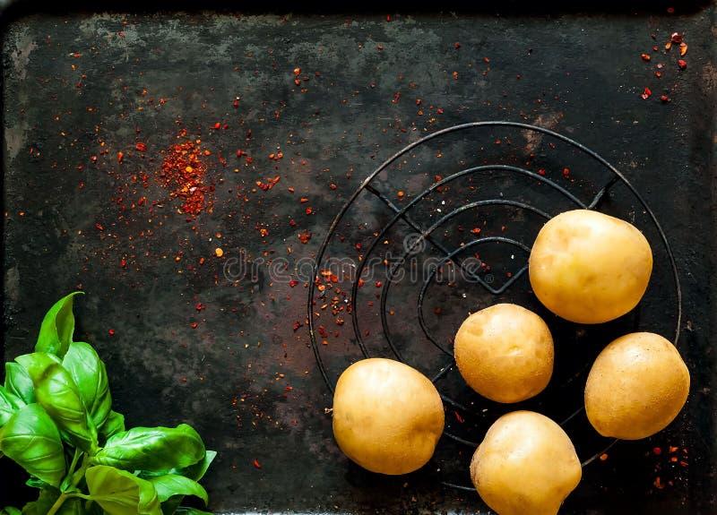 烹调的未加工的土豆在老金属黑暗的葡萄酒背景,用香料和菠菜 健康素食主义者食物n 库存照片