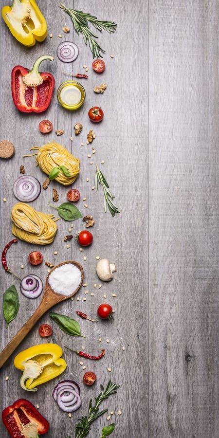 烹调的未加工的面团成份用蕃茄、胡椒、一把木匙子、盐、油、松果和草本在木土气backgroun 免版税库存图片