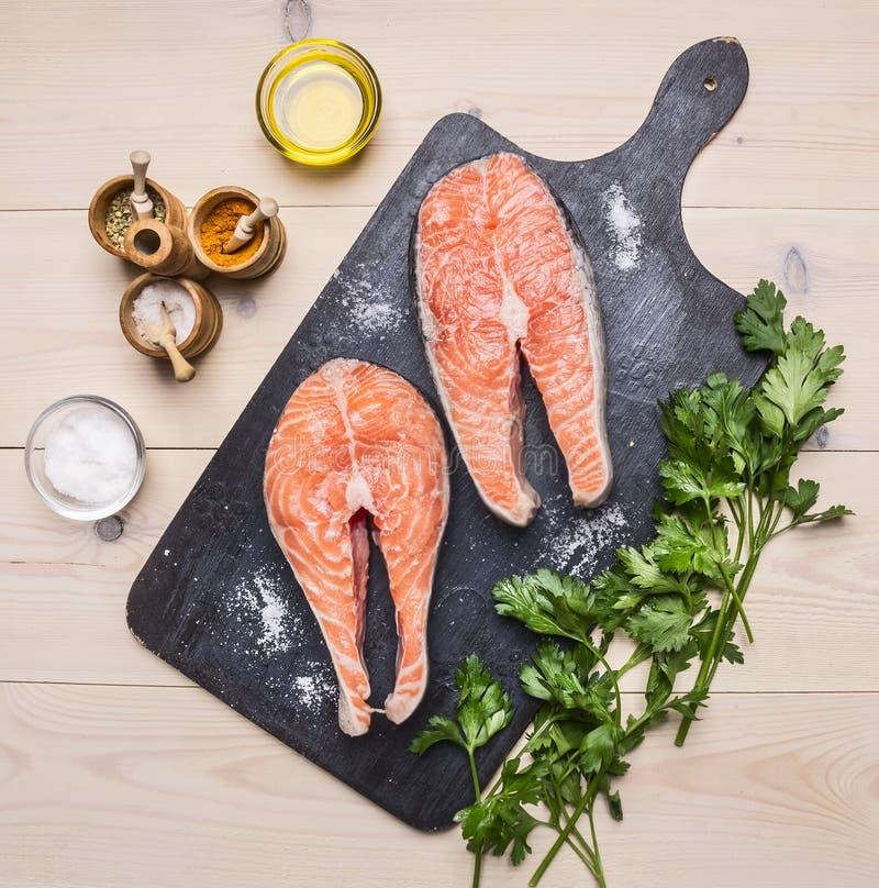 烹调的未加工的鲑鱼排成份用草本、荷兰芹、橄榄油和盐在葡萄酒切板黑暗 库存照片