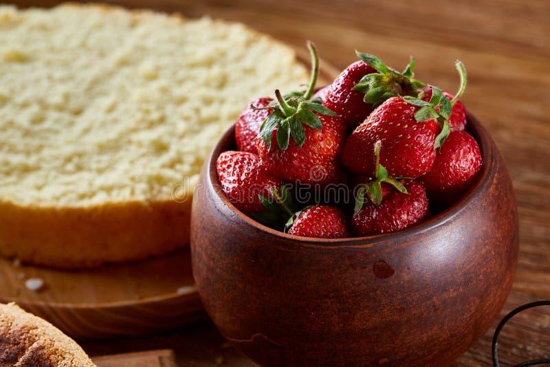 烹调的蛋糕草莓在木背景,选择聚焦的一个碗 库存照片