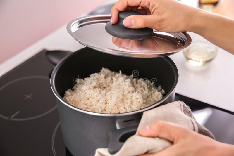 烹调米的妇女在厨房里 免版税库存照片