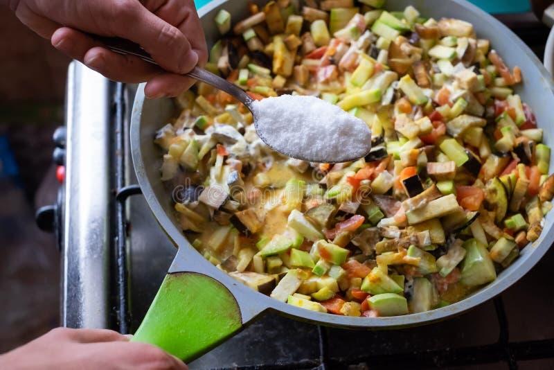 烹调素食膳食 投入许多盐在菜 免版税图库摄影