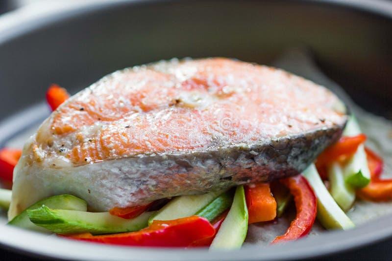 烹调红色鱼三文鱼牛排在菜的,夏南瓜,甜 免版税库存照片