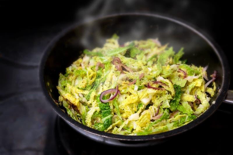 烹调绿色皱叶甘蓝用在一个黑平底锅的红洋葱在火炉,健康冬天菜 库存照片