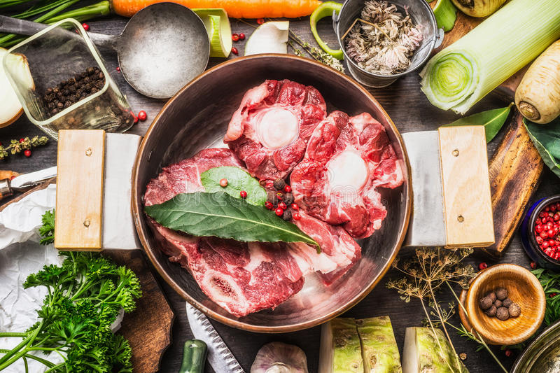 烹调罐用汤或骨头烹调成份和香料在厨房用桌上的汤肉和菜 图库摄影