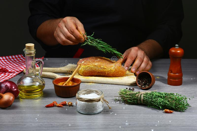 烹调肉用迷迭香的厨师在经典食谱的厨房里在格栅平底锅 烹调在文本或desig的黑暗的背景 库存图片