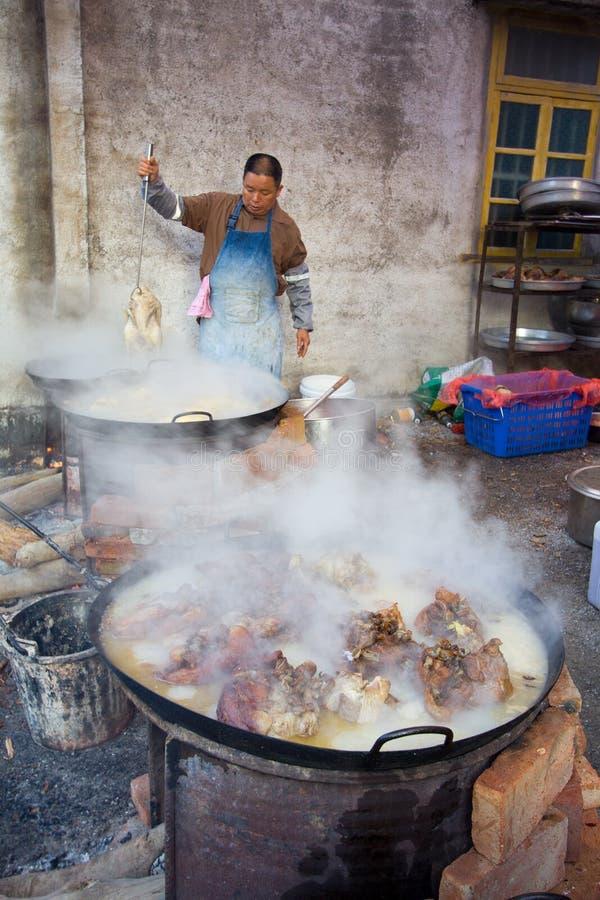 烹调肉的中国乡下厨师