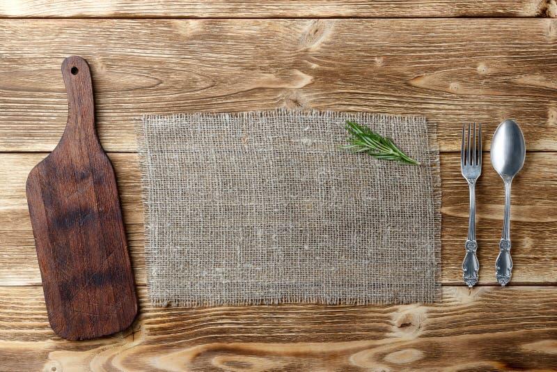 烹调背景概念 葡萄酒切板、麻袋布和利器 顶视图 免版税库存照片