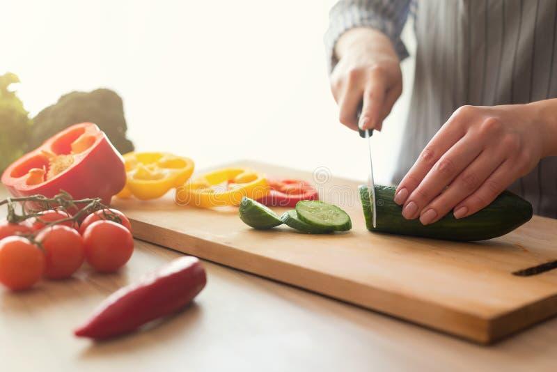烹调菜沙拉的女性手特写镜头在厨房里 免版税库存照片