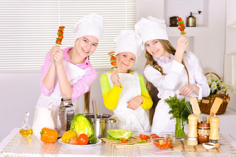 烹调菜盘的愉快的逗人喜爱的女孩 库存照片
