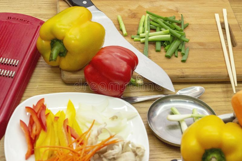 烹调蔬菜菜肴 在切板是辣椒粉和被切的大葱 免版税库存图片