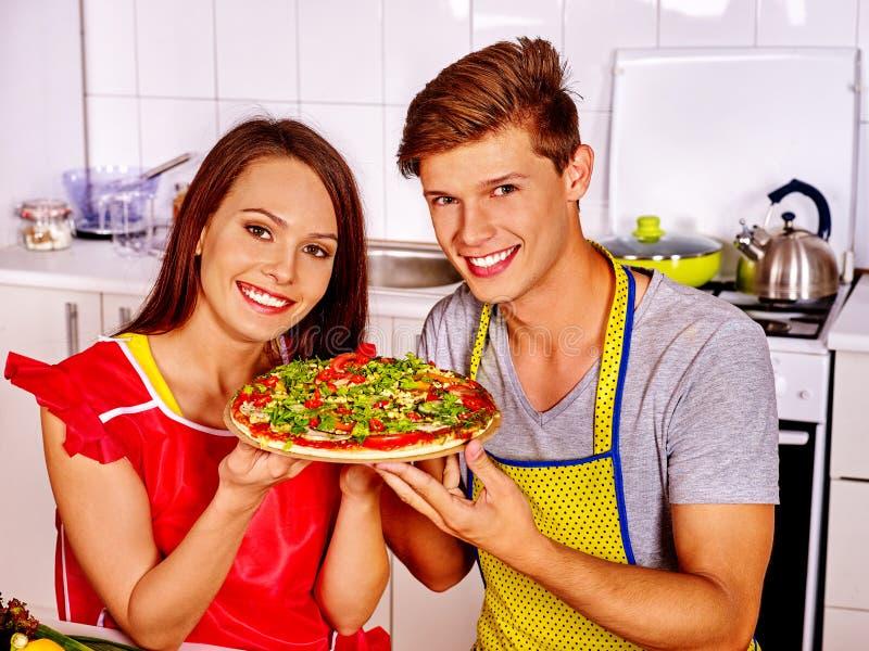烹调薄饼的年轻家庭在厨房 图库摄影