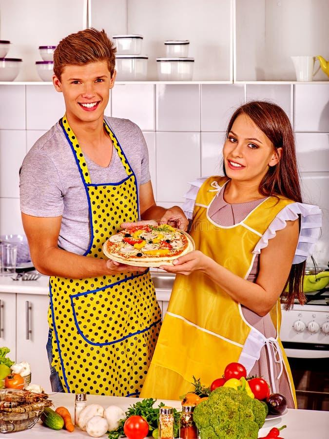 烹调薄饼的年轻家庭在厨房 库存图片