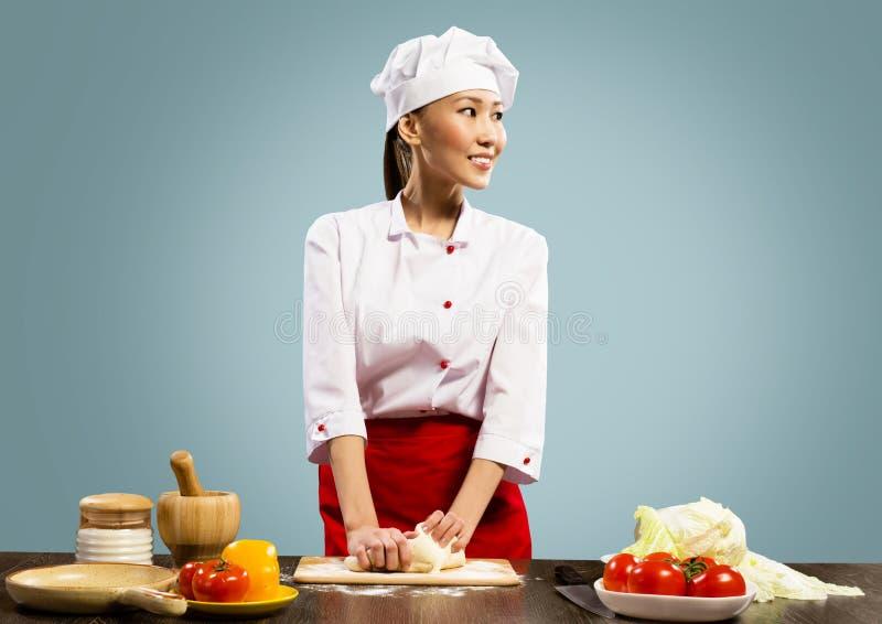 烹调薄饼面团的亚裔女性主厨 免版税库存图片