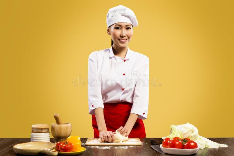 烹调薄饼面团的亚裔女性主厨 免版税库存照片