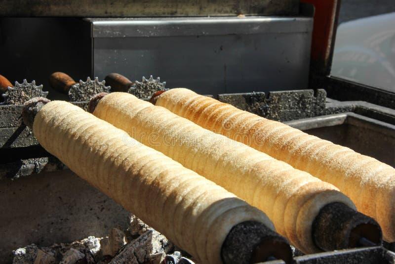 烹调被裹糖衣的卷,传统甜酥皮点心,街道食物,Trdelnik在布拉格 免版税库存图片