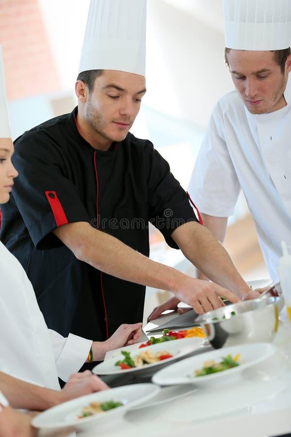 烹调训练年轻学徒的厨师 图库摄影