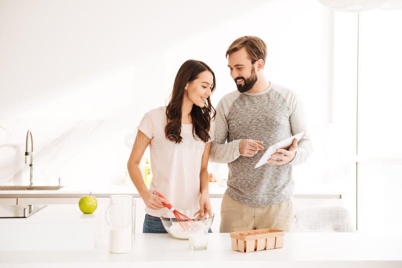 烹调酥皮点心的愉快的年轻夫妇 免版税库存图片