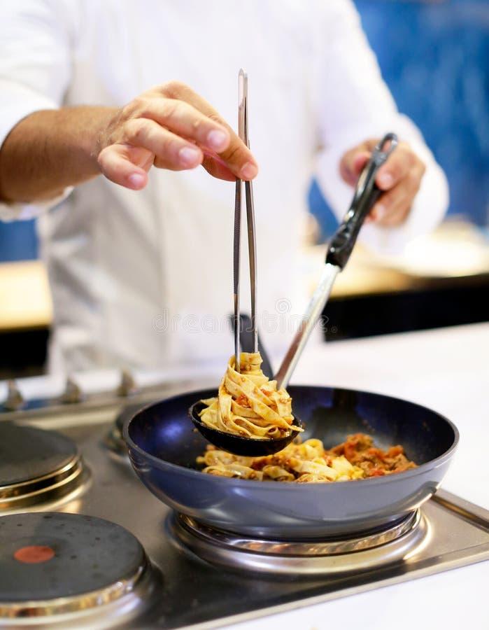 烹调面团,厨师的厨师在厨房里服务在板材的意粉carbonara 图库摄影