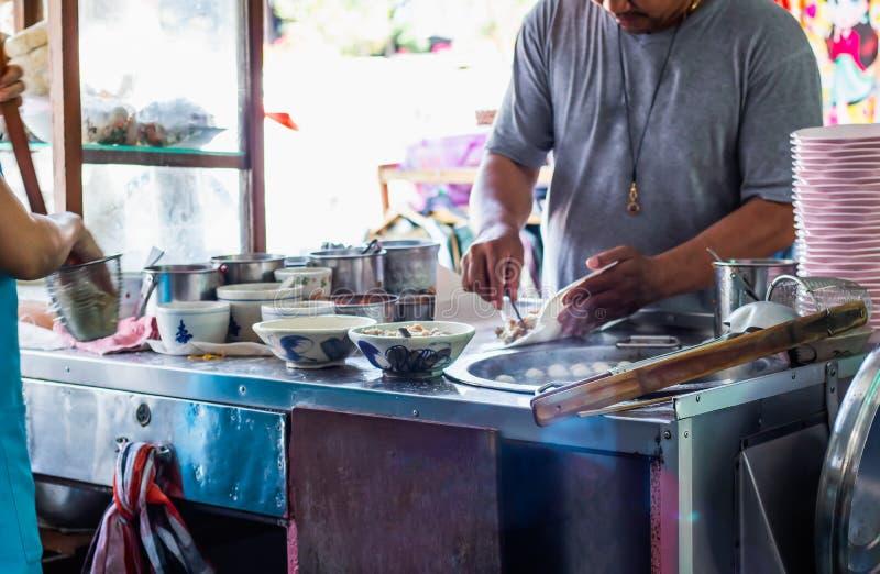 烹调面条的厨师在面条商店曼谷,泰国街道食物 库存图片