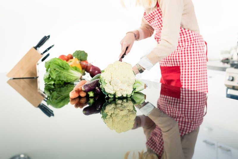 烹调食物的亚裔妇女的反射 图库摄影