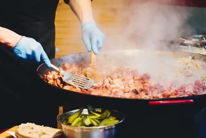 烹调食物的厨师在街道 免版税库存照片