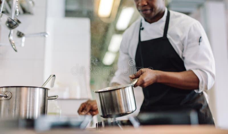 烹调食物的厨师在餐馆厨房 免版税图库摄影