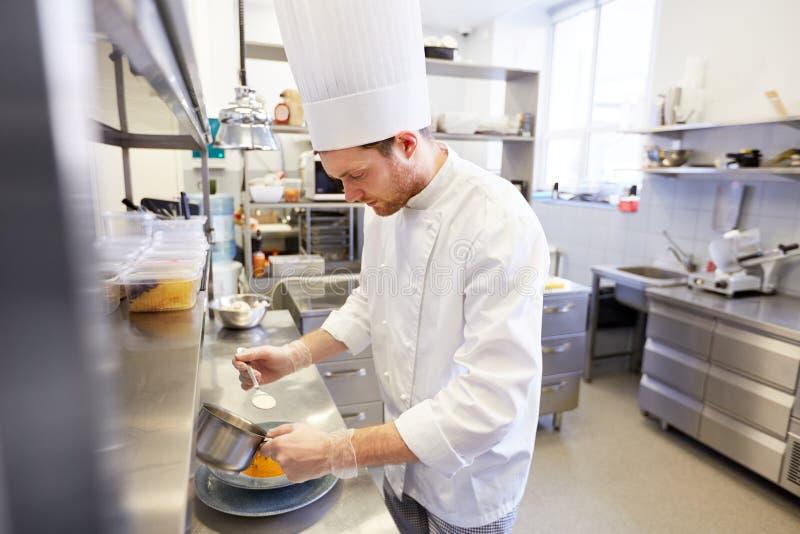 烹调食物的愉快的男性厨师在餐馆厨房 免版税图库摄影