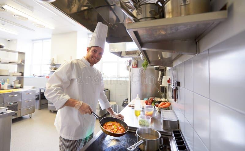 烹调食物的愉快的男性厨师在餐馆厨房 免版税库存图片