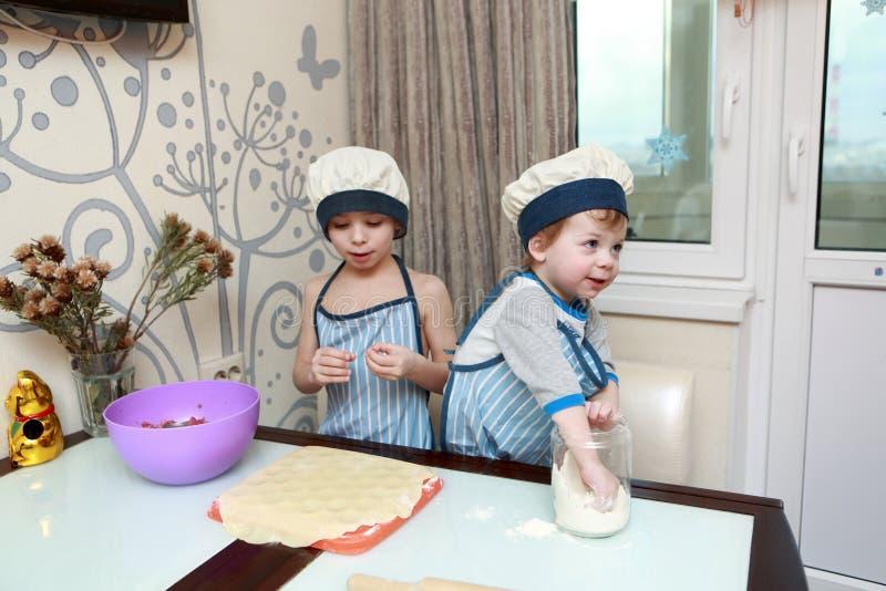 烹调饺子的两个孩子 免版税库存图片