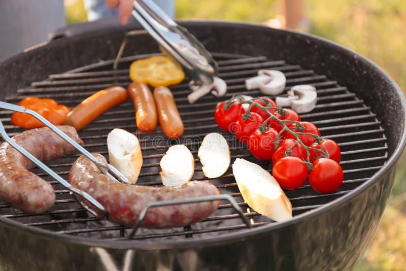 烹调香肠、面包和菜在烤肉格栅,特写镜头 库存图片