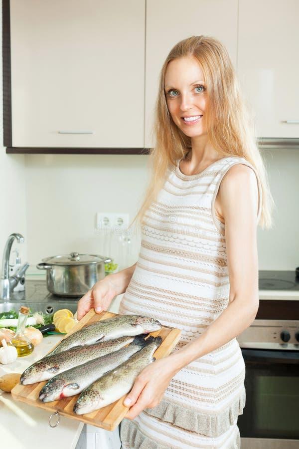 烹调鳟鱼的微笑的女孩钓鱼用在煎锅的柠檬在成套工具 免版税库存图片