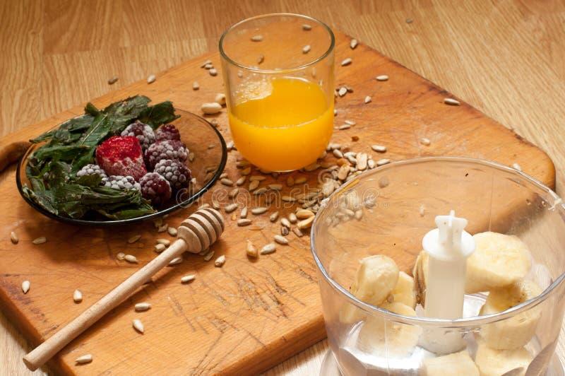 烹调,橙汁、香蕉、结冰的草莓黑莓和种子生动的圆滑的人成份和搅拌器,榨汁器,郁金香 免版税图库摄影