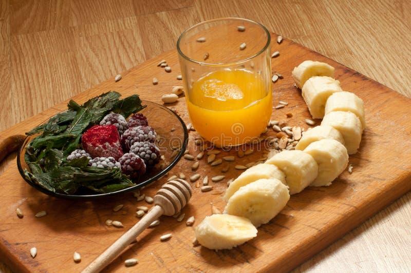 烹调,橙汁、香蕉、结冰的草莓黑莓和种子生动的圆滑的人成份和搅拌器,榨汁器,郁金香 图库摄影