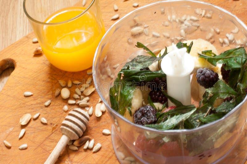 烹调,橙汁、香蕉、结冰的草莓黑莓和种子生动的圆滑的人成份在搅拌器,榨汁器,郁金香 免版税库存图片