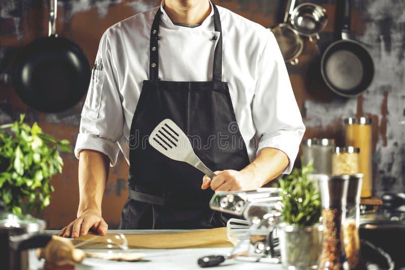 烹调,行业和人概念-做食物的男性厨师厨师在餐馆厨房 免版税库存照片