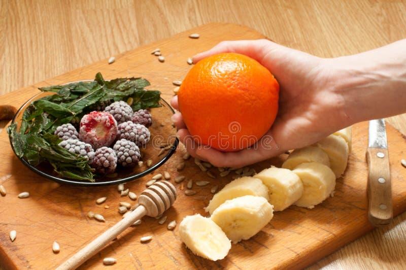 烹调,香蕉,拿着橙色,结冰的草莓黑莓和种子生动的圆滑的人成份和搅拌器,榨汁器, tul的手 免版税库存照片