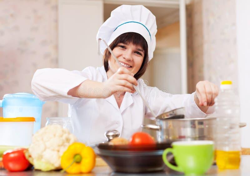 烹调从菜的厨师妇女 免版税库存照片