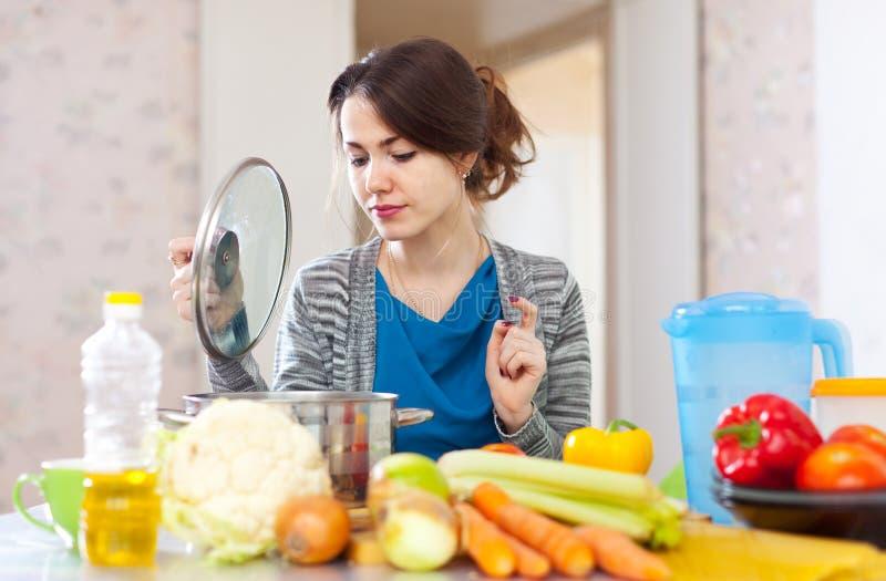 烹调素食午餐的美丽的妇女 免版税库存图片