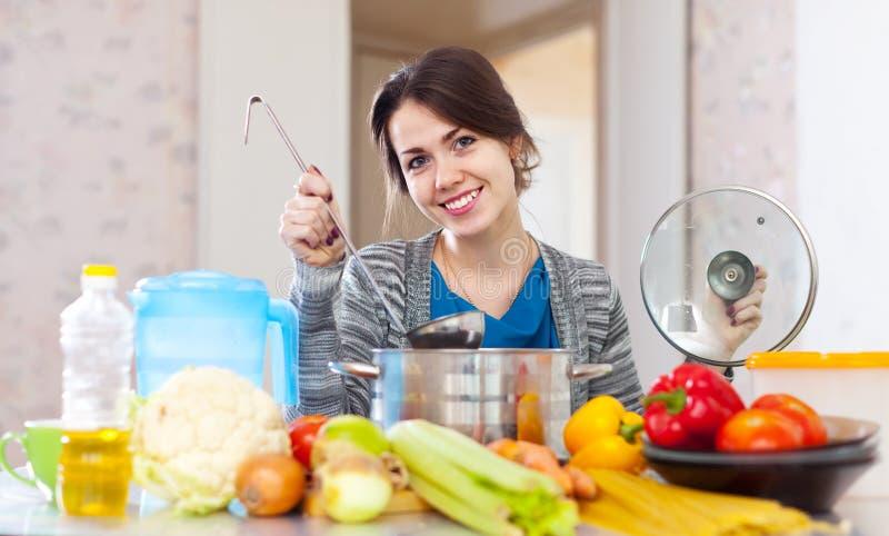 烹调素食者午餐的愉快的少妇 免版税库存图片
