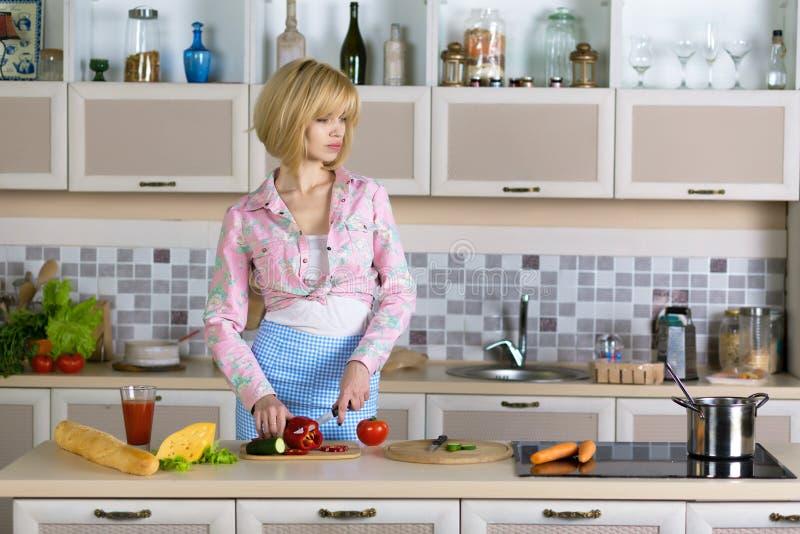 烹调素食膳食的妇女在国内厨房内部 图库摄影