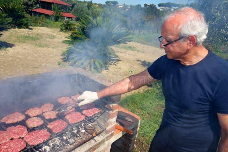 烹调BBQ肉的烤肉年长人 免版税库存图片