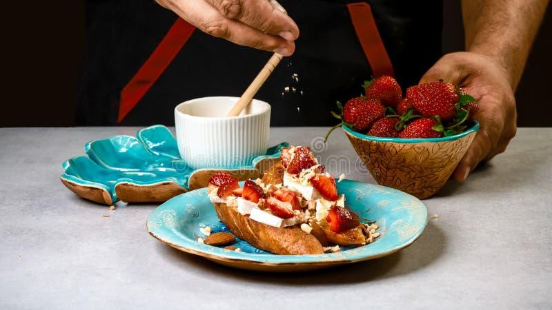 烹调bruschetta三明治用草莓、乳酪和蜂蜜 在木背景的食物食谱 平台面视图从上面 库存照片