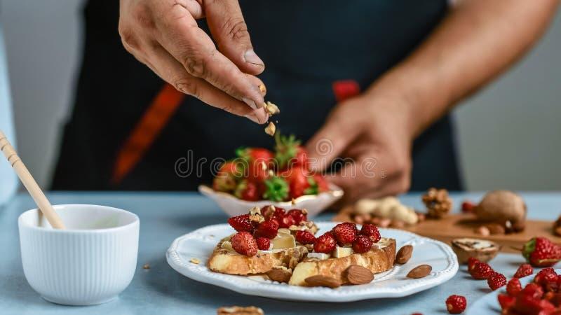 烹调bruschetta三明治用草莓、乳酪和蜂蜜 在木背景的食物食谱 平台面视图从上面 免版税库存图片