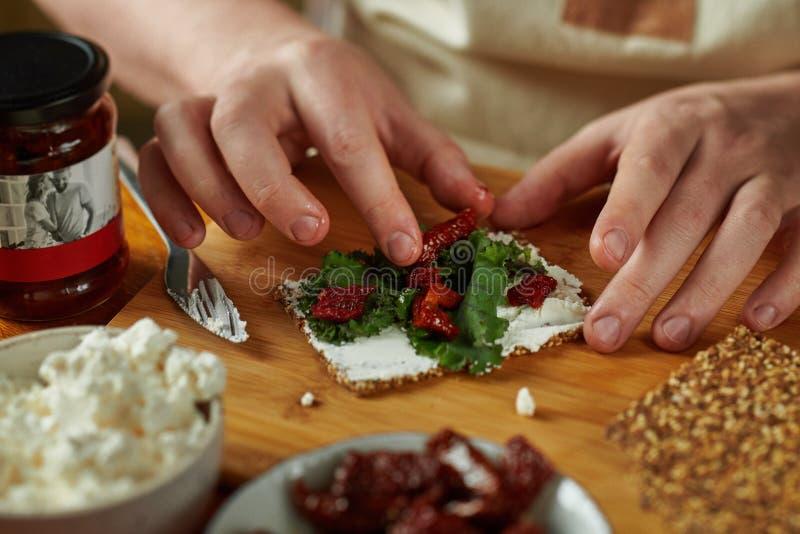 烹调bruschetta,在框架的仅手的人 免版税库存图片