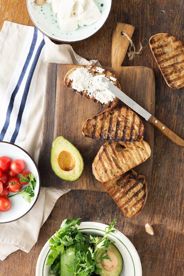 烹调Bruschetta 希腊白软干酪、西红柿和鲕梨 它 库存图片