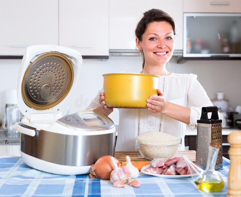 烹调pilau的微笑的妇女 库存图片